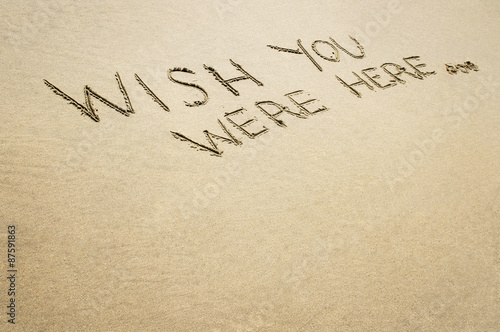 Photo  Words wish you were here written in the sand on the beach.