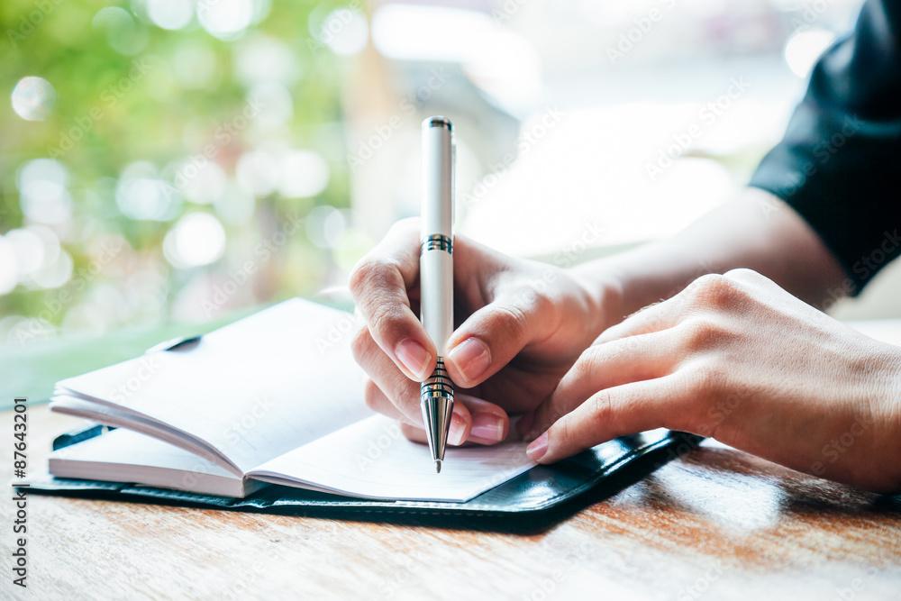 Fototapeta close up of woman writing her journal