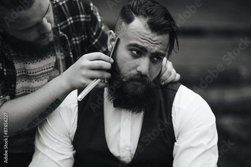 Fotografering barber shaves a bearded man