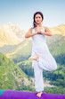 Beautiful woman relaxing and meditating outdoor at mountain