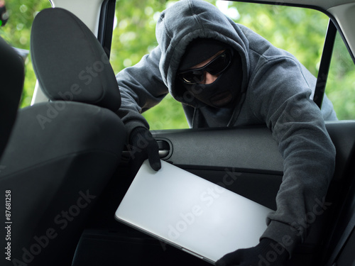 Photo Car theft - a laptop being stolen through the window of an