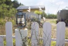 Kerosene Lantern Standing On The Fence. House In The Background