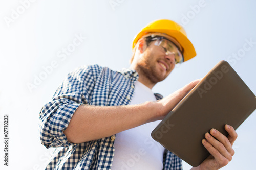 close up of builder in hardhat with tablet pc
