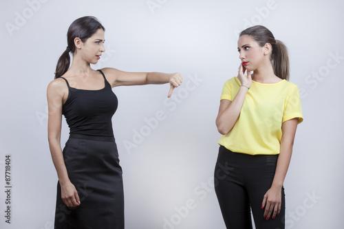 Valokuva  Due ragazza litigano e una mostra pollice verso