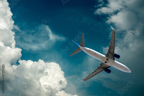 Airplane at flying under sky with clouds Wallpaper Mural