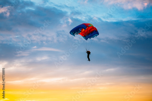 Deurstickers Luchtsport Skydiver On Colorful Parachute In Sunny Sky