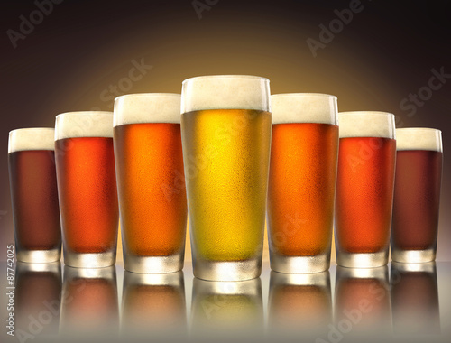 Fotografia  A tasty delicious row of a variety craft brew tap beers in pub glasses on reflec