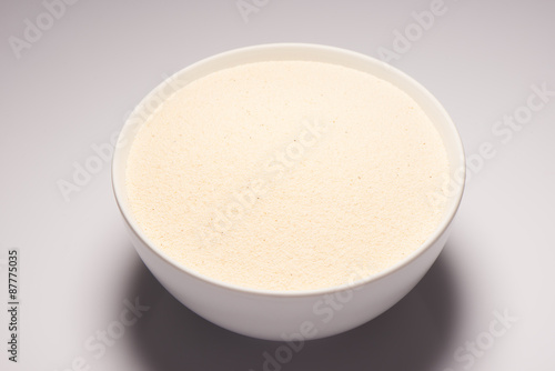 Valokuva  Semolina croup in white ceramic bowl on white background