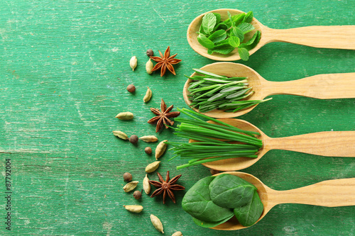 Foto auf Leinwand Gewürze 2 Wooden spoons with fresh herbs and spices on color wooden background