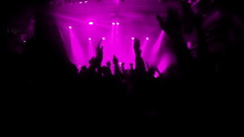 Slow Motion Video Of An Excited Crowd Clapping And Jumpiing On The Rock Concert. Pink Stage Lights Illuminating The Venue.