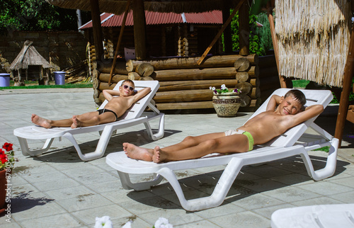 Slika na platnu boys taking a break from swimming and resting on a chaise lounge