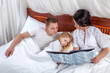 Portrait of a little girl reading with her parents in bed