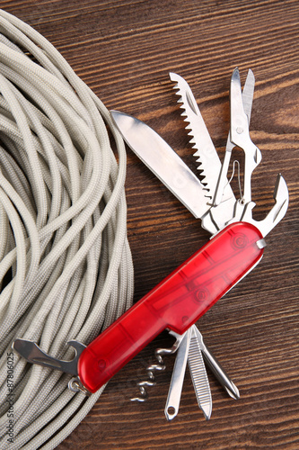 Foto  Multipurpose knife on wooden background