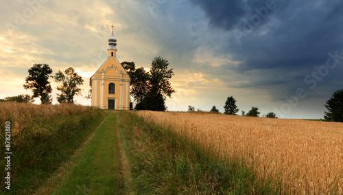 Fototapeta Kościółek na wzgórzu, pola, chmury. obraz