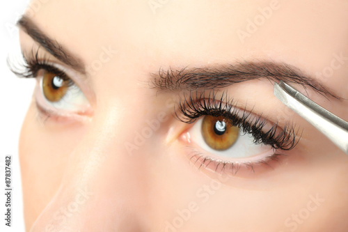 Fotografering  Young woman plucking eyebrows with tweezers close up
