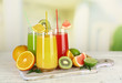 Glasses of different juice with fruits and mint on bright background