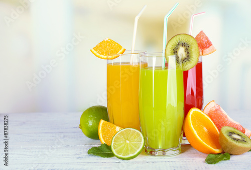 Recess Fitting Juice Glasses of different juice with fruits and mint on bright background