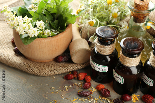 Photo  Herbs, berries and flowers with mortar, on wooden table background