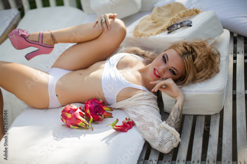 Fototapety, obrazy: Woman sunbathing in bikini at tropical travel resort. Beautiful young woman lying on sun lounger near pool