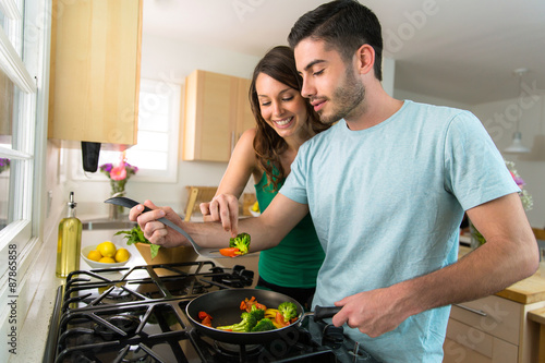 Staande foto Koken Young attractive couple preparing dinner on a date saving money by cooking at home
