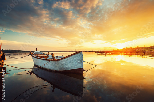 Sunset over calm lake and boat, sky reflecting in water Fototapeta