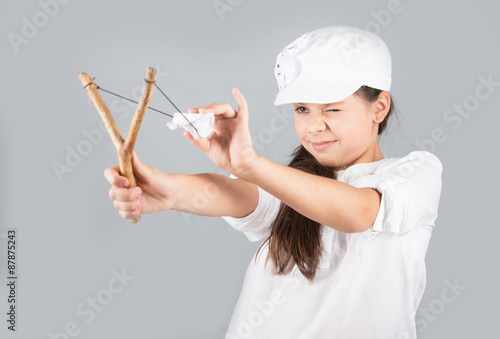 Valokuva  Preteen girl in white cap with a slingshot