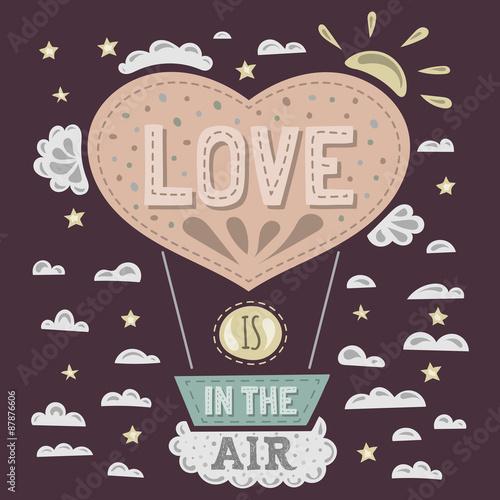 balon-w-ksztalcie-serca-z-napisem-love-is-in-the-air-na-tle-chmurek-i-slonca