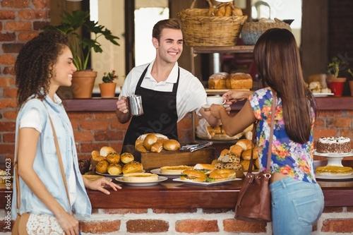 Deurstickers Bakkerij Smiling barista offering coffee to pretty customer