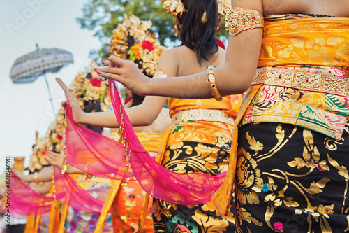 Group of beautiful Balinese girls in bright traditional costumes - sarongs decorated by hindu Barong and Garuda masks. Arts and culture of Bali island and Indonesia people and asian travel backgrounds