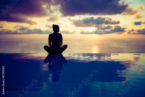 Fotografia  Woman sitting on the edge of the pool