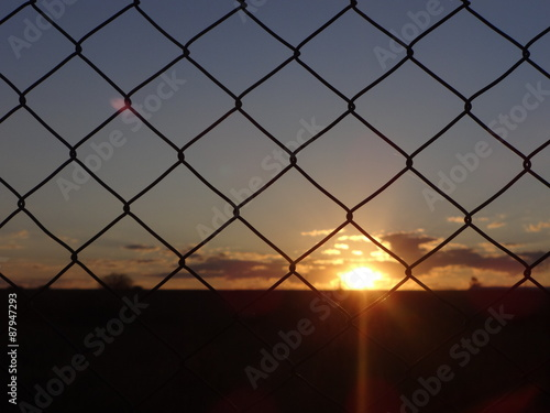 Puesta del sol a través del alambrado Wallpaper Mural