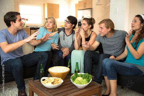 Large group of friends at a party get together house drinking beer chatting stor Poster