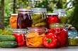 Leinwanddruck Bild - Jars of pickled vegetables and fruits in the garden
