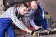 Two car mechanics at workshop