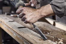 Hands Of Carpenter With Chisel In The Hands