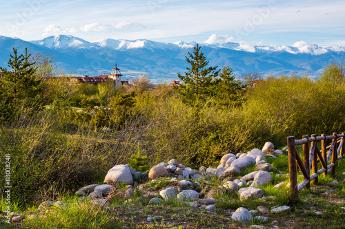 Photo sur Aluminium Kaki Spring landscape with wooden fence, trees, part and snowy mountains