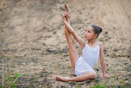 Tuinposter Gymnastiek Девочка тренируется на песке