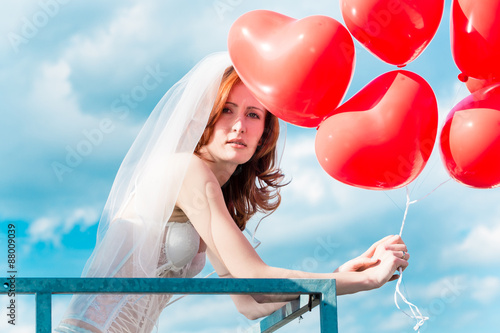Obraz na plátně Bride with red balloons on balcony in lingerie