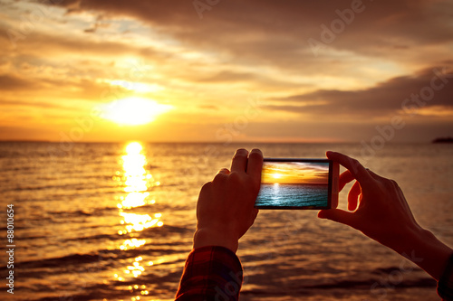 hands holding mobile phone at sunset