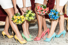 Row Of Bridesmaids With Bouquets Of Flowers And Shoes Of Different Colors