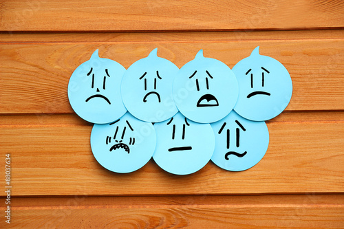 Fotografie, Tablou  Sad emotions on blue stickers on wooden background