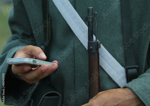 Photo Historical re-enactment with a soldier and a smartphone