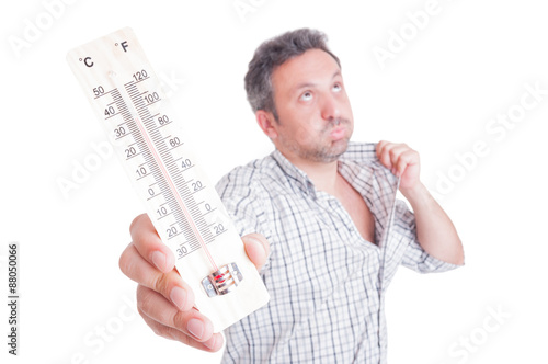 Fotografie, Obraz  Sweaty man holding thermometer as summer heat concept