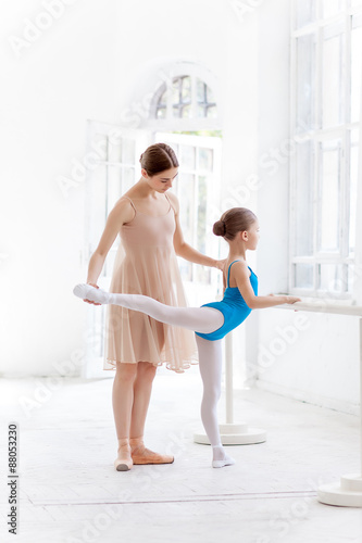 Fényképezés  The little ballerina posing at ballet barre with personal