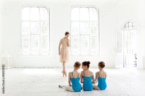 Fényképezés  Three little ballerinas dancing with personal ballet teacher in