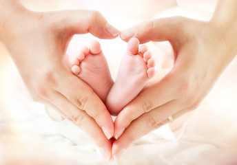 Fototapeta Do gabinetu lekarskiego/szpitala baby feet in mother hands - hearth shape