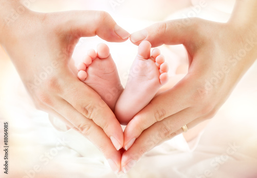 Fényképezés  baby feet in mother hands - hearth shape