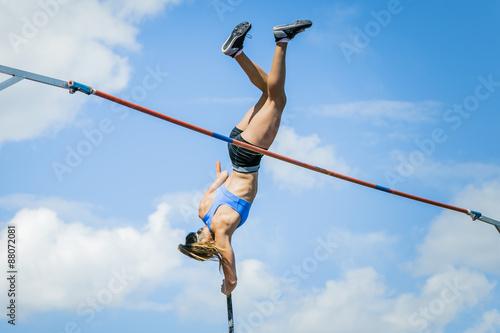 Fotografia  Girl athletes pole vault seems to reach the sky