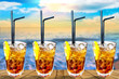 Four Cuba libre exotic tasty cocktail with beautiful sunset bac