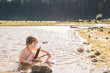 Boy sitting in lake collecting feathers